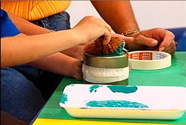 daubing paint on tuna tin with sea sponge
